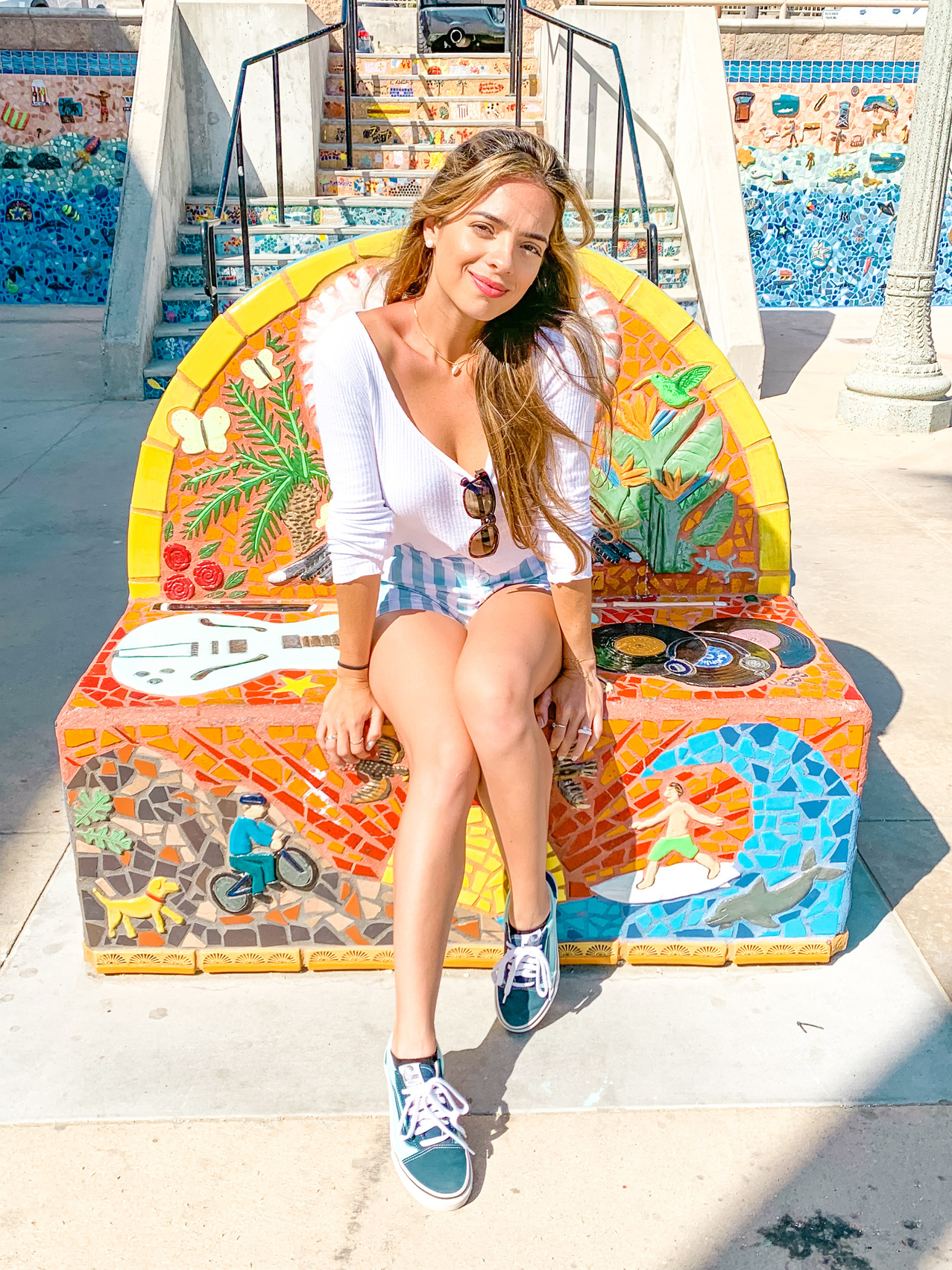 girl sitting on a mosaic bench