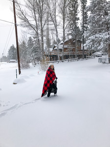 girl walking in snow with red blanket