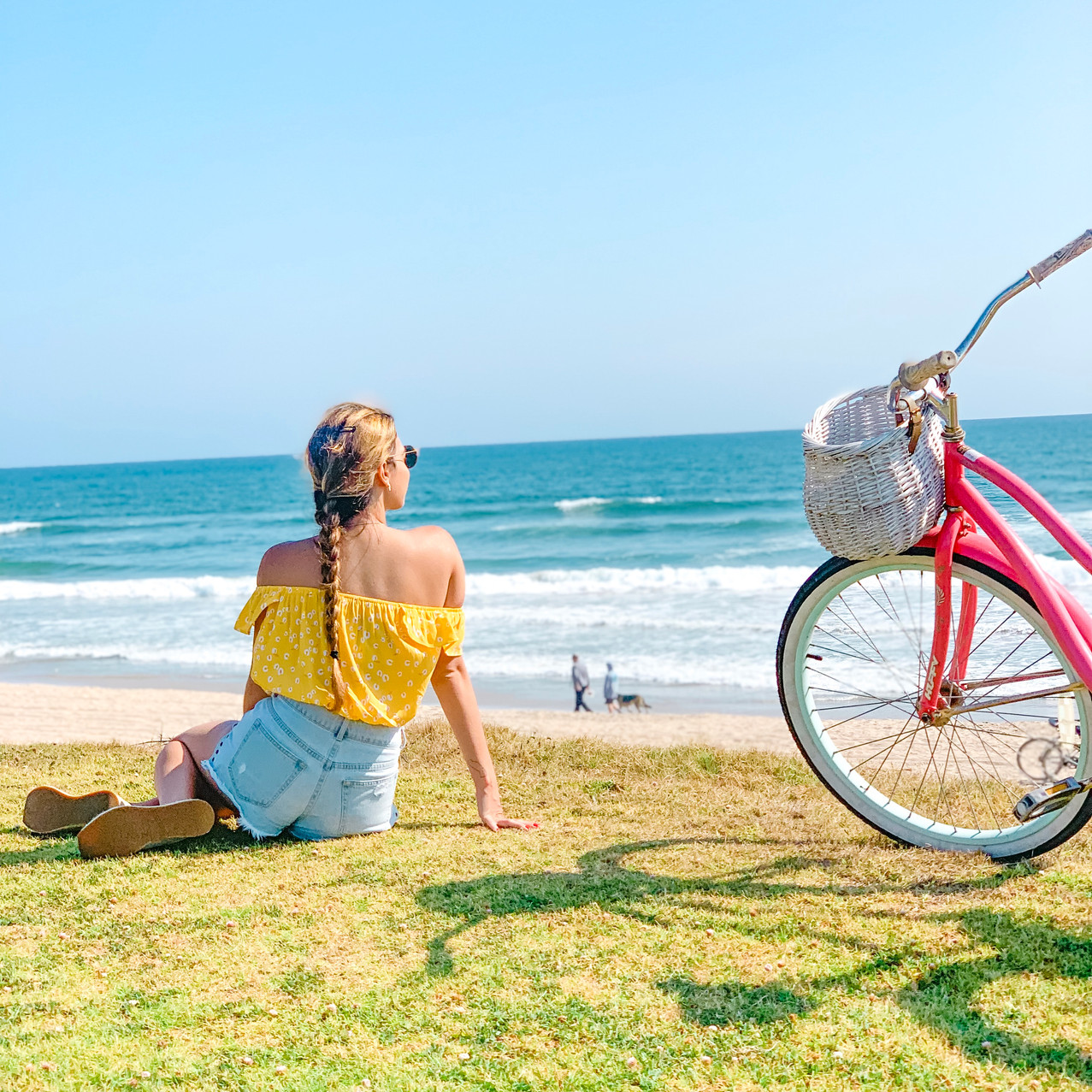 girl sitting on the lawn overlooking the ocean next to a pink bicycle