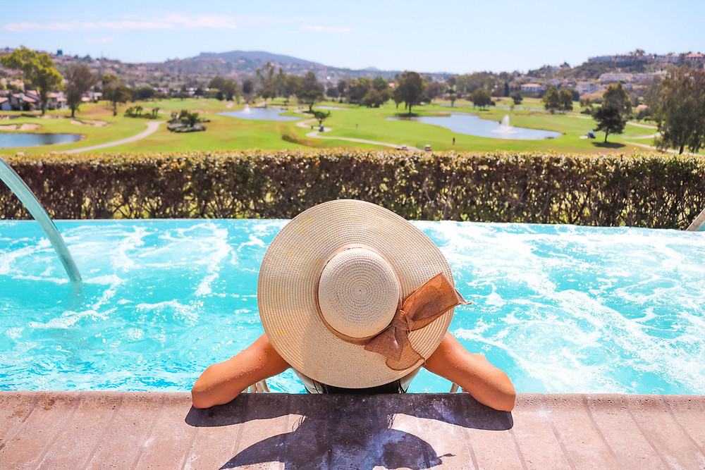 girl wearing a straw hat in a pool overlooking a golf course