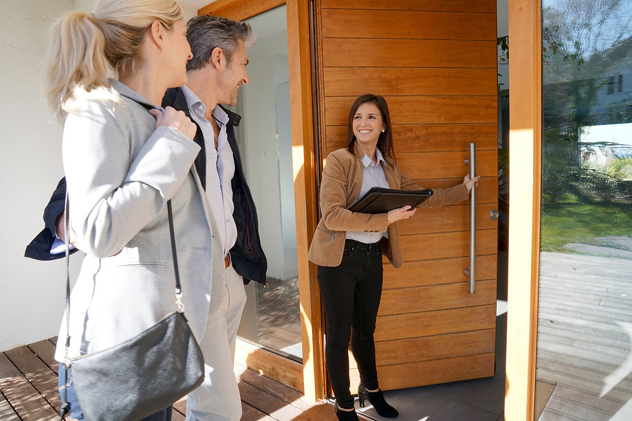 Real estate agent inviting couple to ent