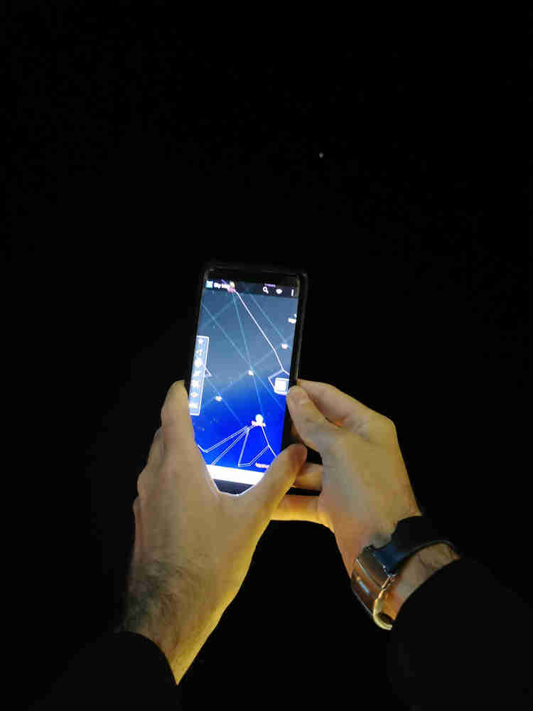 He's holding up his phone, showing an app that maps the stars in the sky