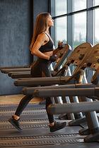 sportswoman-running-on-treadmill-in-gym-