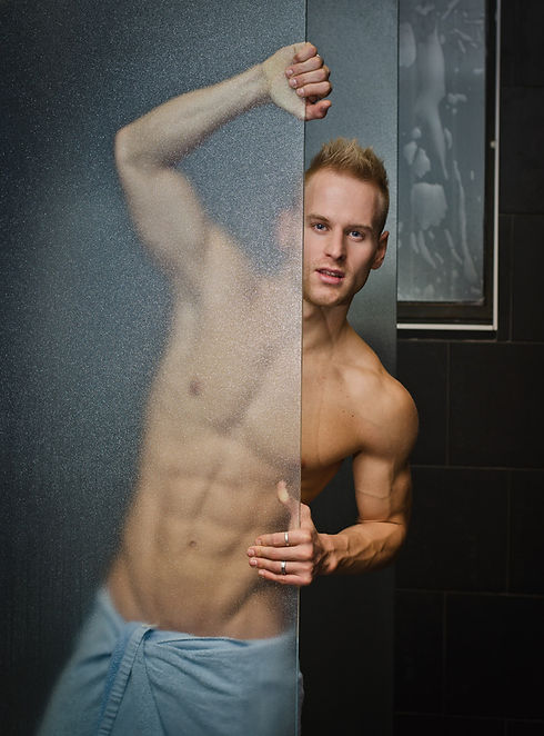 A male wearing a towel wrapped around him looking around the side of a glass shower screen