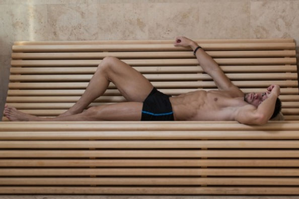 Male wearing black shorts laid down on a wooden bench in a sauna
