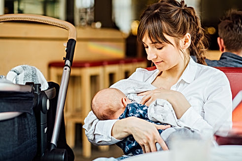 A young mother is breastfeeding her baby