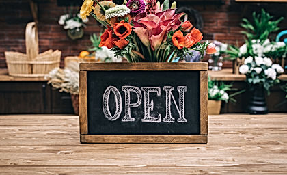 Open sign on wooden table among flowers