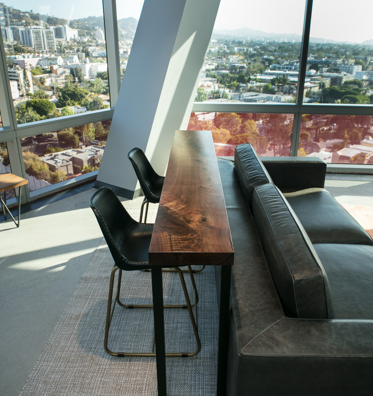 Modern contemporary walnut bar top tables in high rise hollywood office space.