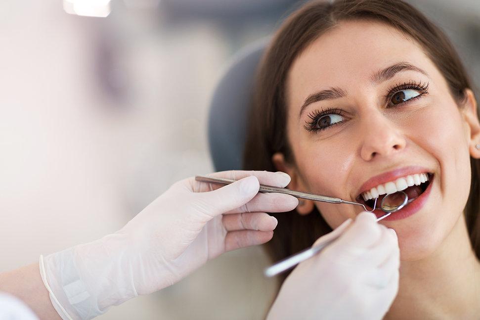 Woman having teeth examined at dentists.