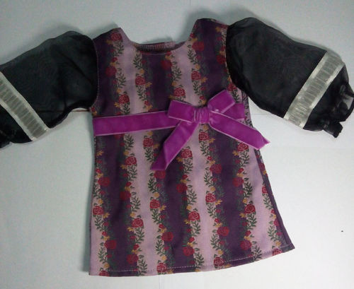 American Girl Doll: This dress has black see-through material sleeves with white ribbon and elastic at the tops. The dress itself is a purple and lavender striped pattern with red roses and gold and green stems placed on the borders of each stripe. There is a light purple velvet bow on the bodice of the dress.