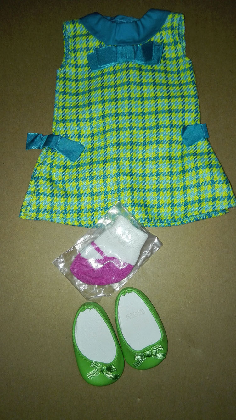 American Girl Doll: The socks are wrapped in a plastic bag. They are white socks with purple trim on each sock. They only cover up to the doll's foot. The dress is a green dress that has plaid patterns all over it. The plaid pattern is light blue, dark blue and yellow. The yellow is just dots. The Peter-Pan collar on the dress is blue. There is a blue bow on the bodice of the dress, and matching blue bows on ethier side of the dress. The dress has a Velcro closure. The flats are green and they have bows on the front. The inside of the shoes are white. The right shoe has a code that is not visible in the image.