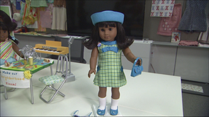 """The Melody Ellison doll features brown eyes, dark skin and the Sonali mold. She has bangs and shoulder length, thick black hair that is flipped at the ends. Her arms and legs can be posed, and her head can move from side to side. Her eyes open and close as you lay her down and pick her up. Her meet outfit includes a green plaid dress with a blue collar on the front. Also, there is a big bow on her dress, as well as two smaller bows on the sides. She will come with a blue headband (not pictured) with a bow on it. Her socks are white and can scrunch up from the start of her feet to her knees. Her shoes are blue flats with a black bottom and have blue bows on them as well. Her meet accessories consist of a blue beret-style hat which is made out of felt, a patriotic colored pin that says, """"Equal Rights '63"""", a blue purse with a bow on it that has a Velcro closure and blue striped sunglasses."""