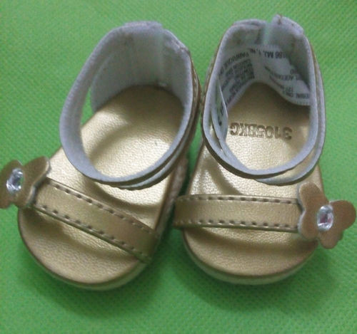 "Golden sandals with a golden strap. The strap has a butterfly on it. The butterfly features a rhinestone on it. The right shoe has a copyright tag on it as well as the code ""31058XC"" printed on it. Velcro closure, probably."