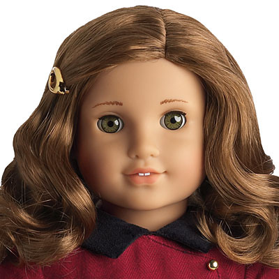The Rebecca Rubin doll has honey brown curly hair, light skin, feathered eyebrows, and yellow-hazel eyes. In this photo, she is pictured in her meet outfit from her release on May 31, 2009 to the BeForever revamp of the historical American Girl dolls on August 28, 2014. Rebecca is from 1914, just a couple of years before World War One, so she is in a red dress with a Peter-Pan collar, a golden button that is non functional and a golden hairpin that is the same color as the button. In this outfit, she came with the book Meet Rebecca.
