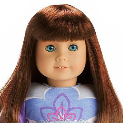 """This custom edit of a American Girl doll has dark auburn hair, light skin, lined eyebrows and seafoam eyes. She is actually Just Like You 8 edited. The Just Like You 8 doll that was available from 1995 until 2008 had red hair, light skin, lined eyebrows and lazer green eyes. The edited doll is shown in the top of the """"I Like Your Style Outfit"""" which has a light blue crisp front with a dark blue flower design, a purple smaller flower design, a even smaller pink flower design and has a white flower design that is the smallest of all and goes across the pink flower. The sleeves are purple and have the white flower design all over then, except that they are blue. Dolls in this outfit came with a book that was titled """"Sparkle, Spirit, Style!' and also came with a CD with a pop song, """"I Like Your Style"""", on it."""