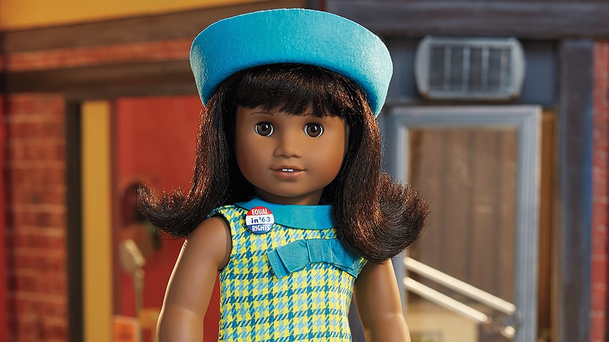 """American Girl Doll: The Melody doll has brown eyes that open and close, and she has thick shoulder-length black hair with full pie bangs and a """"flip"""" at the end. She comes with a green dress with a blue Peter Pan collar, a dark blue, light blue and yellow plaid pattern, one big bow on the bodice of her dress and two smaller matching bows on the skirt of the dress. She is wearing a blue felt beret-style hat and a red, white and blue pin that reads """"Equal in '63 Rights"""". She is standing next to a red brick building with black and yellow trim, a silver address plate and a silver functional door."""