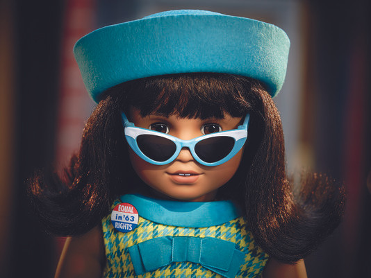 "American Girl Doll: The Melody doll has dark skin, the Sonali mold, thick black shoulder-length hair that is flipped at the end with bangs and brown eyes. Melody is wearing a green plaid dress with a blue collar and a blue bow. Her accessories will include a blue felt beret-style hat, blue sunglasses with a white top and a patriotic colored pin that says ""Equal in '63 Rights""."