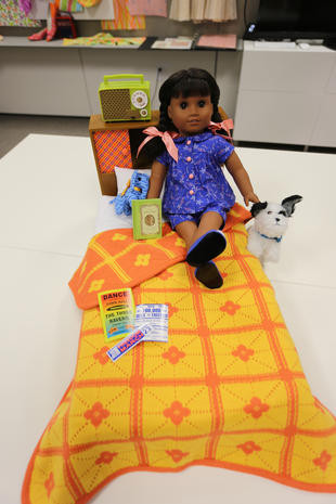 """Melody is wearing her pajamas. Her pajamas consist of a blue star-print top with pink buttons in the middle, two hairbows held on by srunchies, matching blue star-print shorts, and blue flats. Her dog, Bojangles, is a white furry stuffed dog with black ears and a blue tied collar. Her bed features a yellow blanket with orange stiching and a orange clover design with a yellow dot in the middle. The reverse side of the blanket has reversed colors. Her bedroom accessories feature three posters of some kind, a """"The Secret Garden"""" book with a green cover, a blue hair net with golden plastic tassels, a brown shelf with a red plaid pattern on the doors, and a green radio with a white netted soundwave, and a white tuner with a golden knob."""