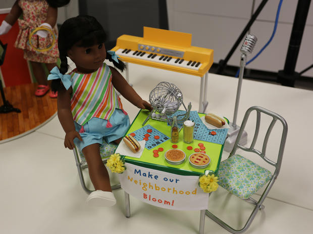 "A Melody doll is wearing Melody's Play Outfit, which consists of two blue hairbows held on by scrunchies, a tank top with colors from ""Fruit Stripe"" Gum, which was a brand of gum that launched in early 1969. The tank top is held on by elastics and has pink yarn tassles. The shorts are chambray blue and have working pockets. The shoes are white flats with bows on them. Melody is seen sitting on a plastic chair with a blue, green, yellow and white design on the chair. The chair looks foldable and is accompanied by a table that has a metal bingo spinner, four BINGO cards, a assortment of red plastic tokens, and food. The food is two hot dogs with mustard on them on two white paper napkins, a green bottle of soda, a white cup of fizzing soda, a apple pie with a patchword design, and a plain pie. The sign on the green table is held on by two corsages of fake flowers, and it reads ""Make Our"" in blue, ""Neighborhood"" in yellow and ""Bloom!"" in red. In the background is a silver microphone on a silver square stand. The microphone has the American Girl Star on it. There is also a yellow piano with working keys in the background, and the piano is held on by 2 sliver sticks."
