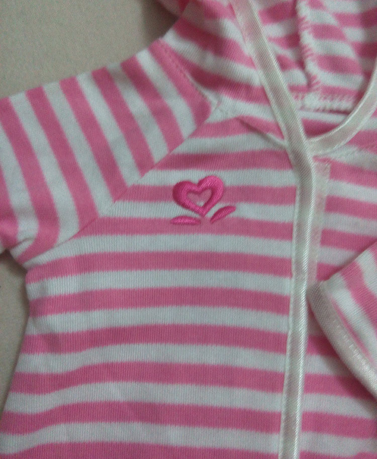 The symbol on the pajamas that tell that the onesie is for the Bitty Baby line. It consists of a pink heart and two lines on each of the heart's sides.