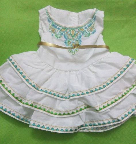 White dress with a Bohemian-style pattern on the bodice. There is a golden belt on the bodice, too. The skirt of the dress has golden stiching and has blue and green triangles on the layers.