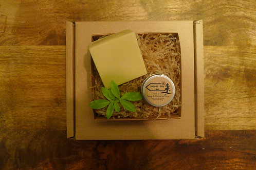 gift set in recyclable box hoeny and almond soap and lip balm sat on a bed of recyclable packing