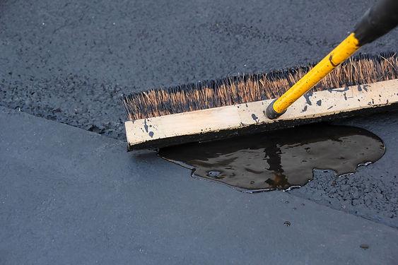 Man sealing asphalt driveway.jpg