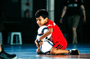 Far Post Academy student holding 3 futsal balls on blue futsal court