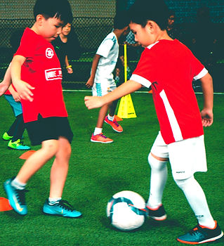 Far Post Academy Futsal Class - Kids kicking futsal ball on green indoor pitch