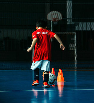 Far Post Academy Futsal Class - Kid running on indoor futsal court with futsal ball and orange cones wearing Far Post Academy training jersey