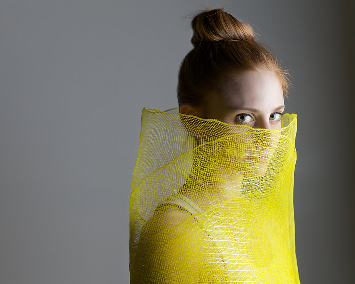 Girl looking at camera wrapped in yelow mesh