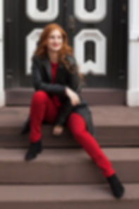 Redhead sitting on steps wearing red and black
