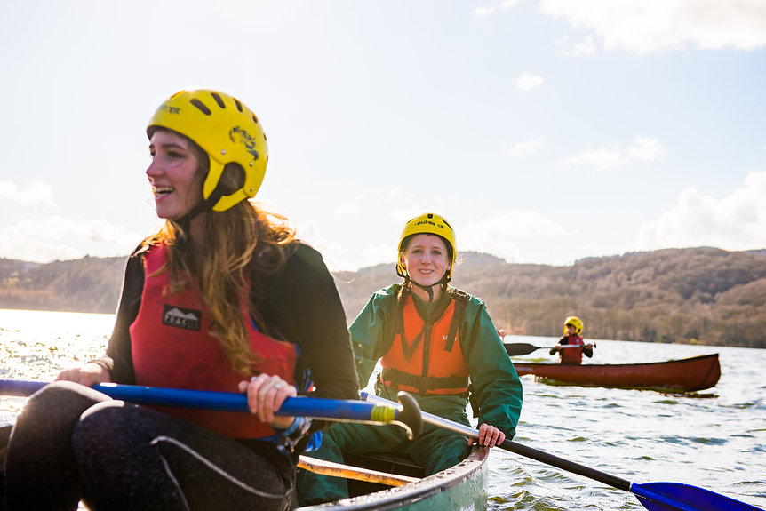 Two female Scouts canoeing on an open lake