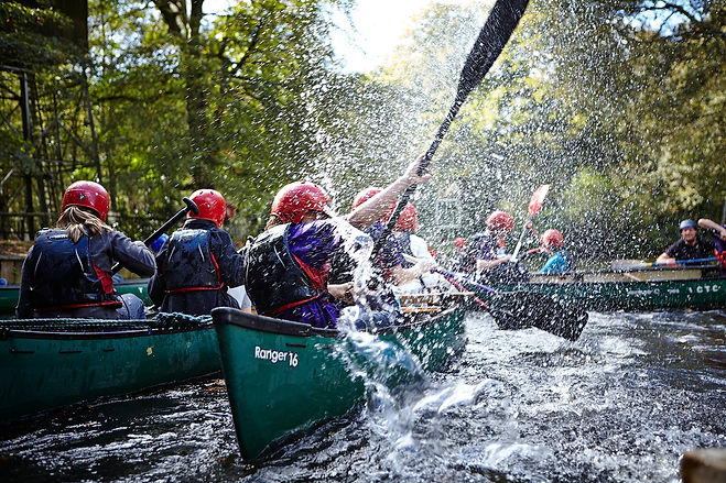 Scouts in canoes, splashing water into the air from their paddles