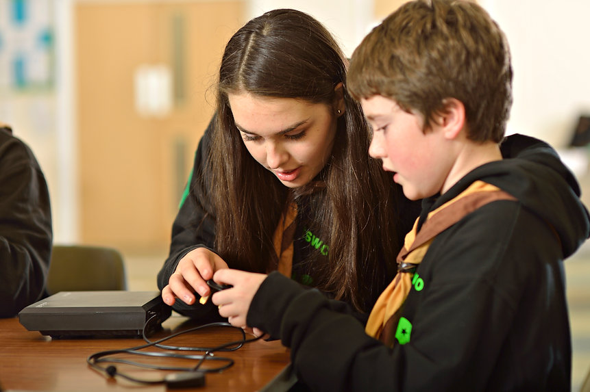 Young Leader Explorer with a Cub interacting with a computer