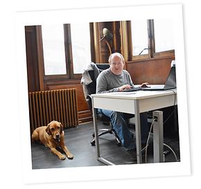 Photo Benjamin et son second chien guide Hermes, au travail dans les locaux de la société