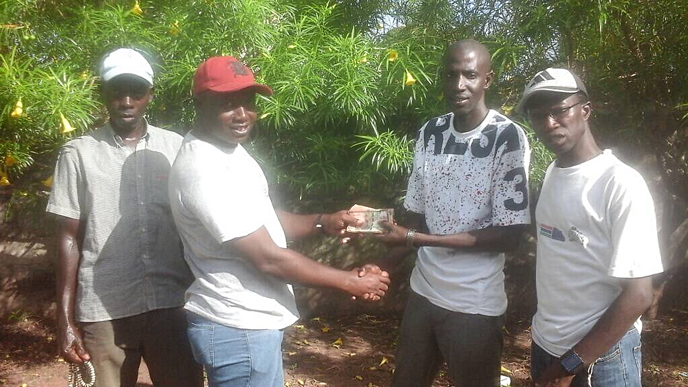 Omar Darboe presenting funds to Environmental Concern Group