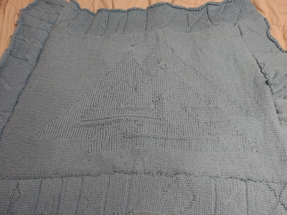 A knitted gray baby blanket.