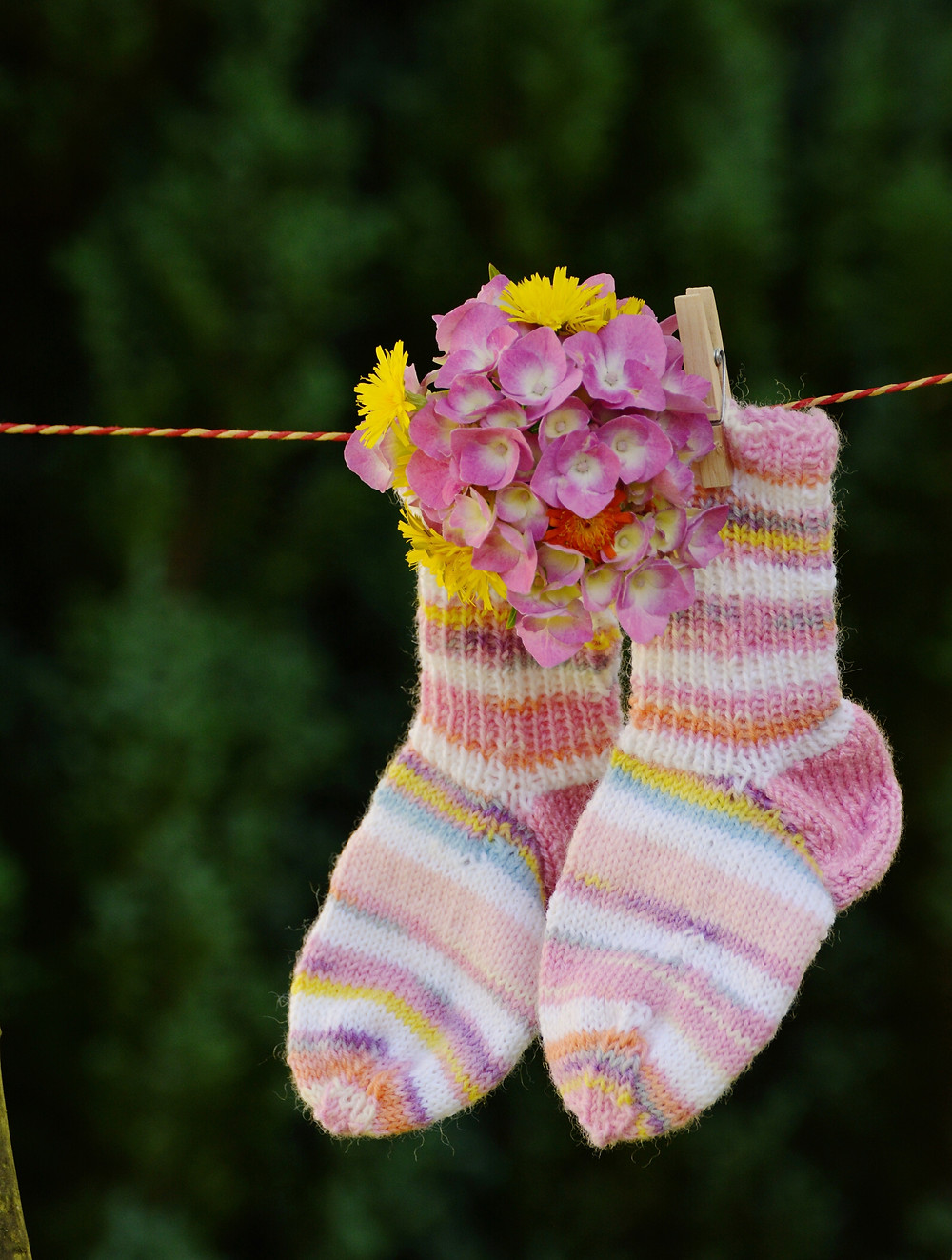 A pair of knitted socks hanging on a clothesline.