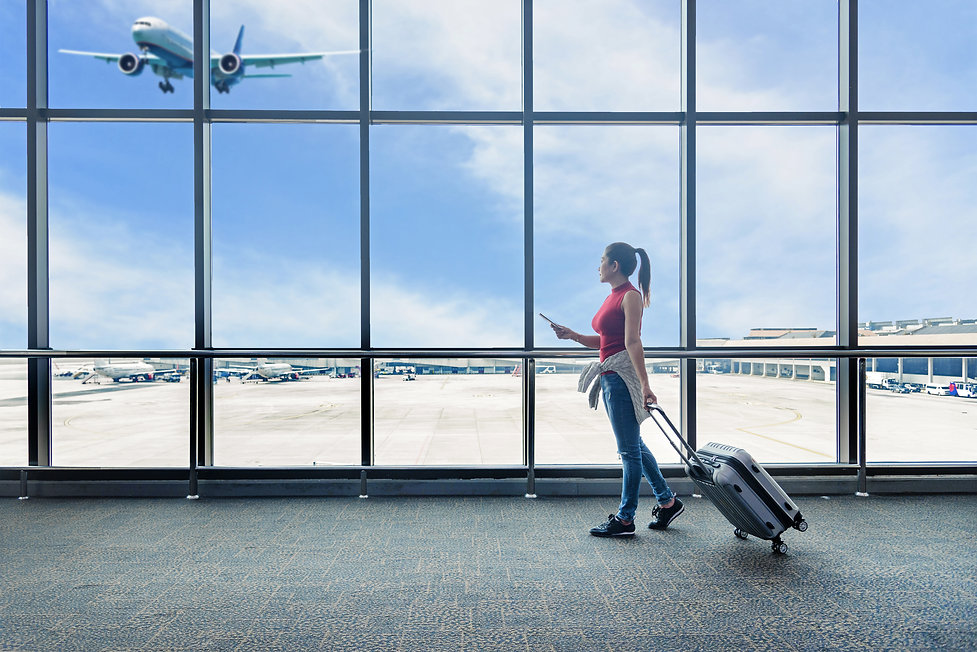 Traveler women plan and backpack see the airplane at the airport glass window. Asian touri