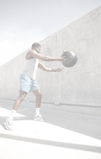 man in white tank top and white shorts holding black ball_edited.jpg
