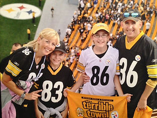 Photo of Drs Martine and Graham Rose and their children at a Pittsburgh Steelers game.