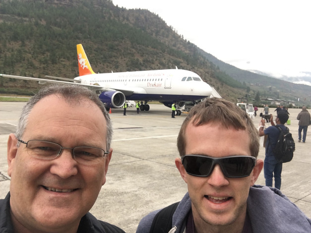 Daryl and Daniel at Paro Airport, Bhutan, with plane and mountains in background