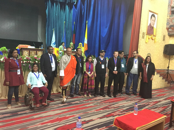 Daniel and other presenters near stage at International Conference on Autism and Neurodevelopmental Disorders, Thimphu, Bhutan