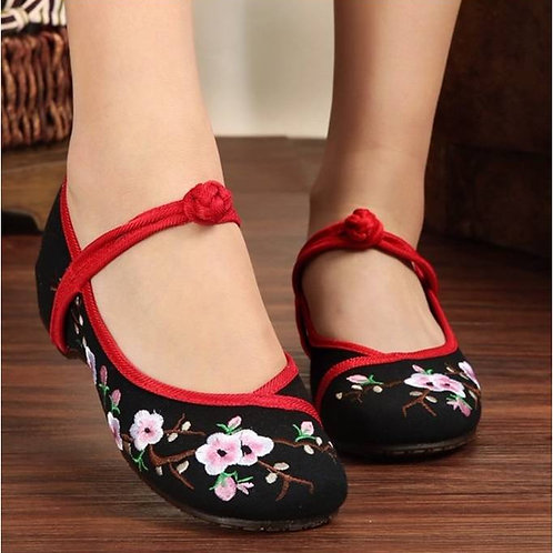Elegant embroidered shoe with low heel, coloured strap and blossom design