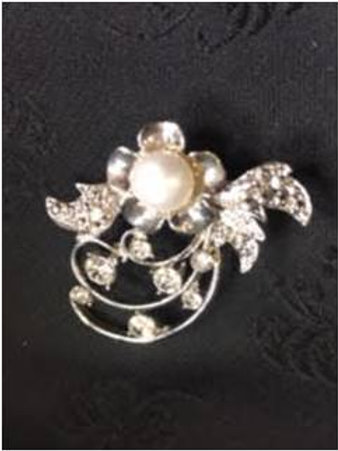 Brooch with natural saltwater pearl laying on a leaf