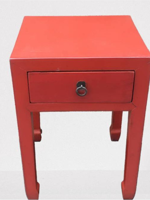 High, red corner table or stand for a vase of flowers