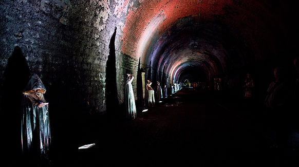 A line of performers in hooded capes lit dramatically in a brick tunnel, part of a performance in the Bristol Biennial 2016.