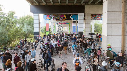 A large crowd of hundreds of Art Spin participants under the Gardiner Expressway looking at series of new mural paintings overhead