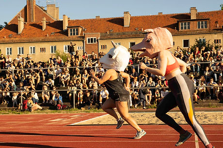 A performance by Hannsjana, picturing two runners wearing animal head masks in front of a large audience in bandstands, at Art Spin Berlin 2018.